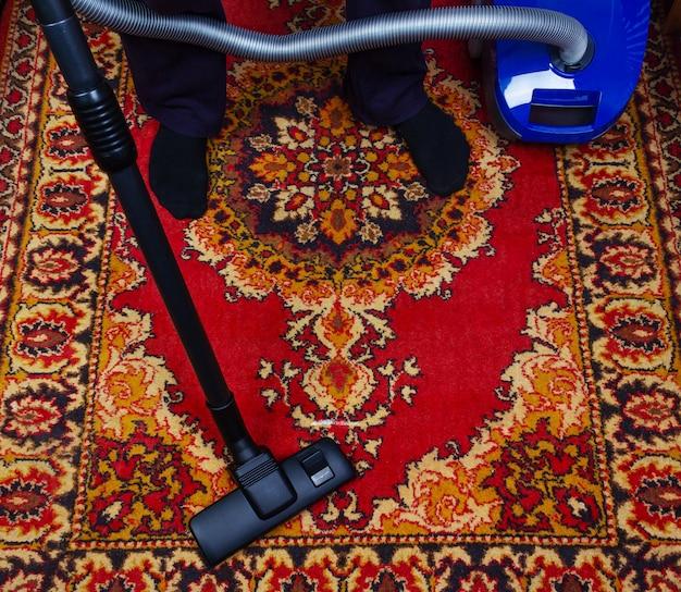 Un uomo pulisce un vecchio tappeto con un aspirapolvere elettrico Foto Premium