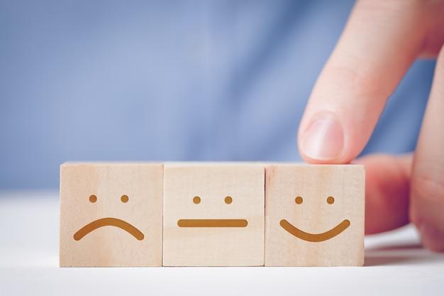 Un uomo punta il dito contro un cubo di legno con una faccia positiva accanto a un uomo neutrale e scontento. per valutare un'azione o una risorsa. Foto Premium