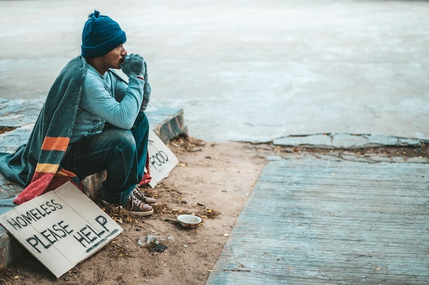 Un uomo seduto mendicanti con senzatetto per favore aiuto messaggio. Foto Gratuite