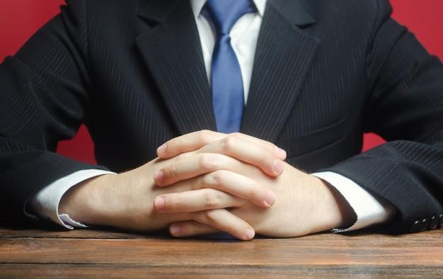 Un uomo si siede al tavolo con le braccia conserte. pronto ad ascoltare notizie e critiche Foto Premium