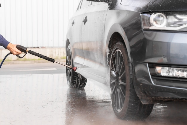 Un uomo sta lavando una macchina in autolavaggio self service. la lavatrice ad alta pressione per veicoli spruzza schiuma. mlada boleslav, 10.12.2019 Foto Premium