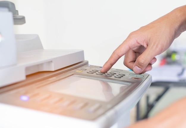 Un uomo sta premendo il pulsante della stampante Foto Premium