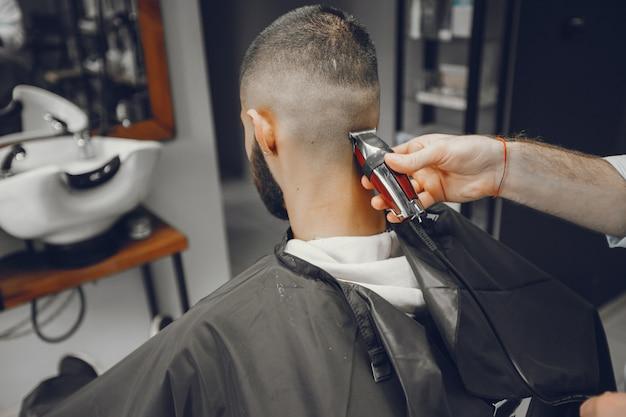 Un uomo taglia i capelli in un negozio di barbiere. Foto Gratuite