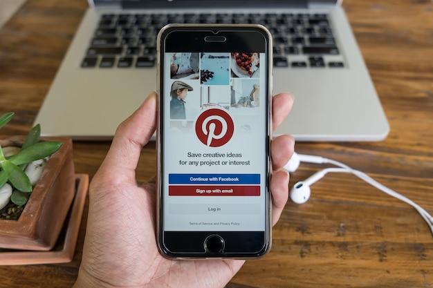 Un uomo tiene apple iphone con l'applicazione pinterest sullo schermo. Foto Premium