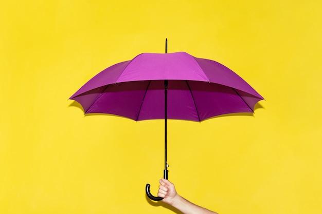 Un uomo tiene in mano un ombrello viola Foto Premium