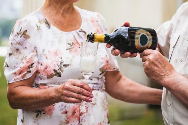 Un uomo versa champagne o vino bianco in un bicchiere della sua amata donna, bevande alcoliche, anniversario, compleanno Foto Premium
