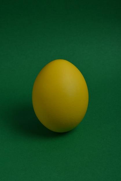 Un uovo di pasqua verniciato giallo stare su uno sfondo verde Foto Premium