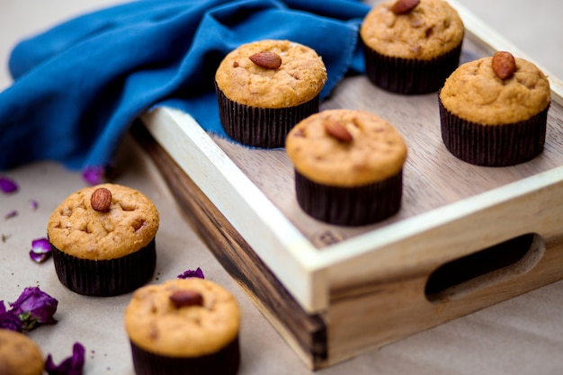 Un vassoio di legno con muffin di base con mandorle in cima Foto Gratuite