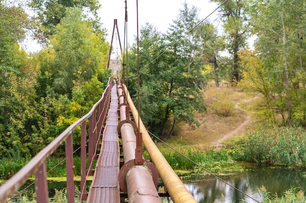 Un vecchio stretto attraversamento del fiume arrugginito, insieme a un tubo di acqua e gas. comunicazioni nel villaggio. Foto Premium