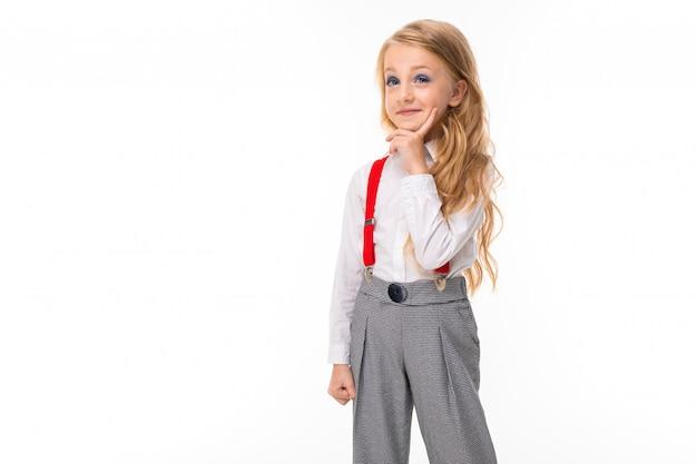 Una bambina con lunghi capelli biondi in una camicia bianca, pull-up rossi, pantaloni in una gabbia, calze rosse e scarpe con brillanti sogni di trucco. Foto Premium