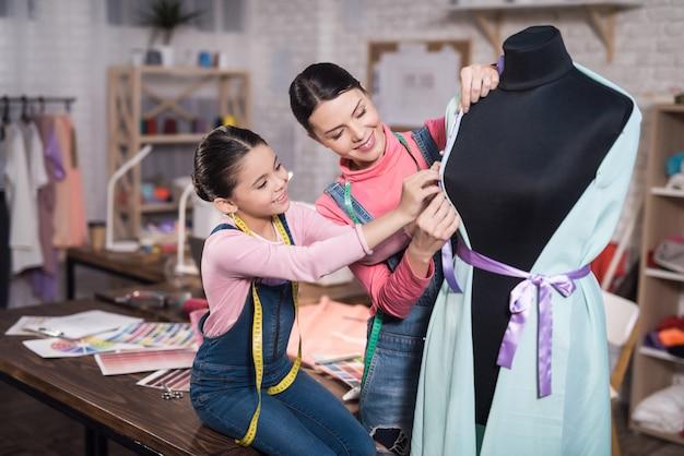 Una bambina e una donna adulta che cercano vestiti Foto Premium
