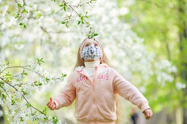 Una bambina in una mascherina medica esamina un fiore dell'albero. Foto Premium