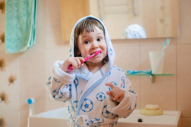 Una bambina lava i denti in bagno. igiene della cavità orale. Foto Premium
