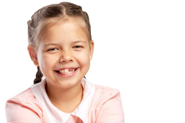Una bambina senza dente davanti sta ridendo. isolato su sfondo bianco. Foto Premium