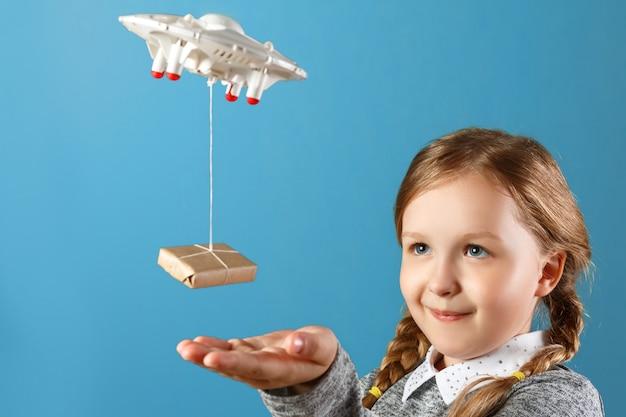 Una bambina si allunga verso una scatola impacchettata legata a un quadricottero. Foto Premium