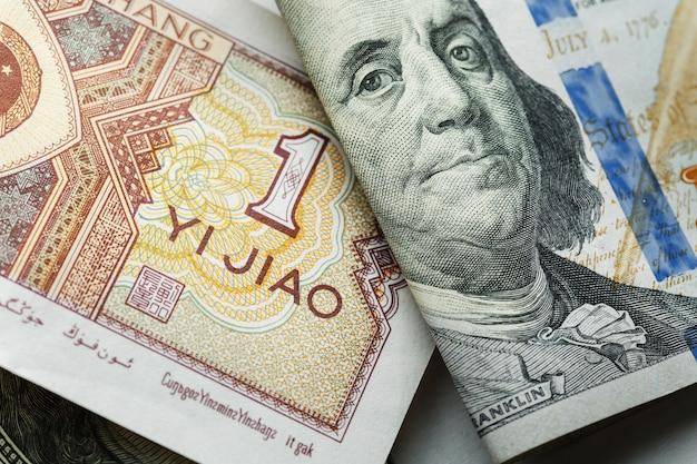 Una banconota cinese di yuan su vari dollari americani Foto Premium