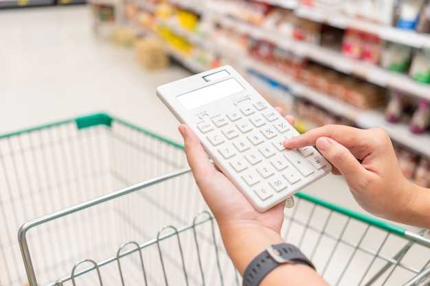 Una bella donna asiatica in possesso di un calcolatore per calcolare il costo e la riduzione dei prezzi Foto Premium