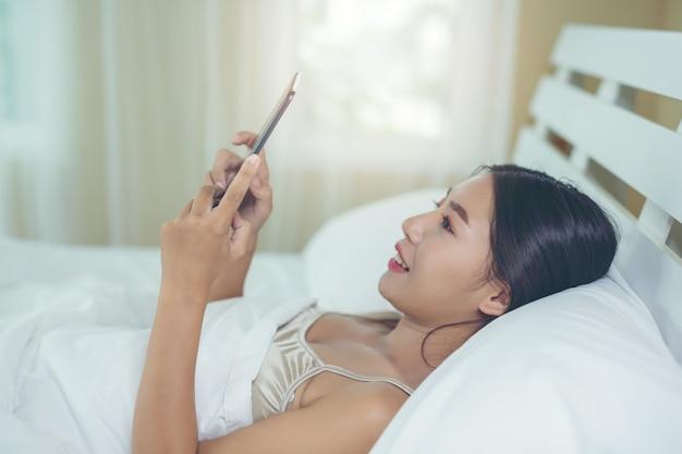Una bella donna asiatica si rilassa e lavora con un computer portatile, leggendo a casa. Foto Gratuite