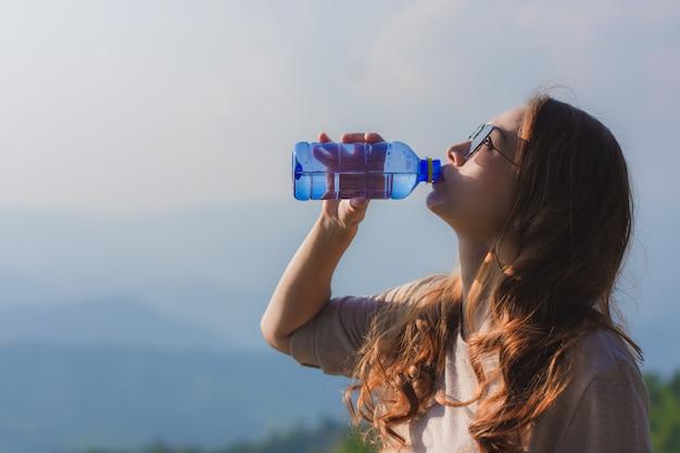 Una bella donna in cima alla collina e acqua potabile Foto Premium