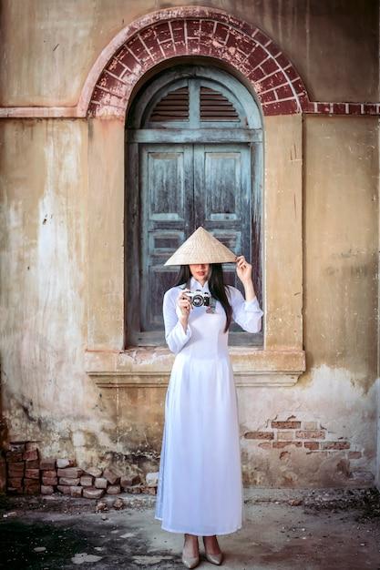 Una bella donna in costume nazionale del vietnam è in piedi e cattura un cappello da sole. mentre fotografi Foto Premium