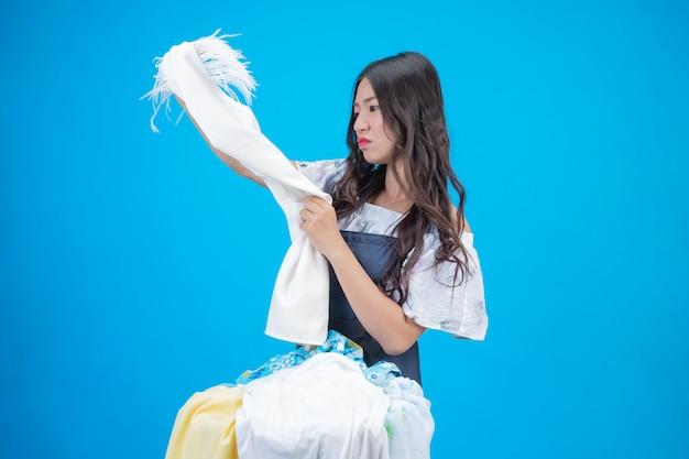 Una bella donna in possesso di un panno preparato per lavare sul blu Foto Gratuite