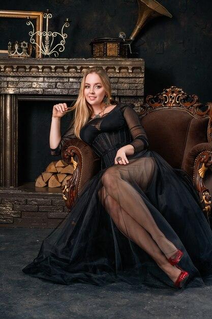 Una bella donna in un abito nero con un corsetto seduto su una sedia in scarpe rosse Foto Premium