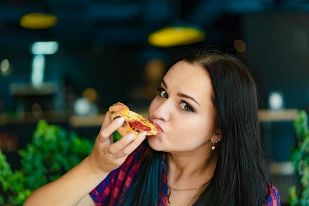 Una bella donna in una camicia a quadri tiene in mano una fetta di pizza e la mangia in una pizzeria. Foto Premium
