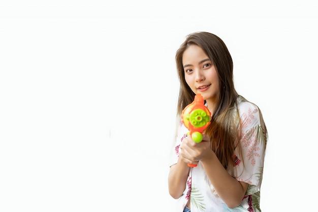Una bella donna thailandese sorridente fresca e felice, nella sua mano in possesso di una pistola ad acqua nel festival di songkran tailandese su uno sfondo bianco. Foto Premium