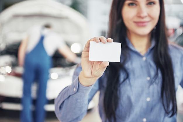 Una bella donna tiene un biglietto da visita del centro servizi auto. il meccanico controlla l'auto sotto il cofano in background Foto Gratuite