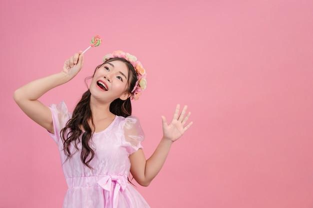 Una bella donna vestita con una principessa rosa sta giocando con le sue dolci caramelle su una rosa. Foto Gratuite