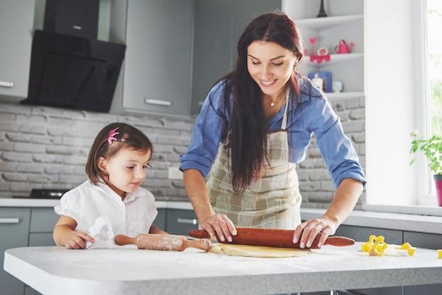 Una bella figlia con sua madre che cucina in cucina Foto Gratuite