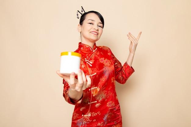 Una bella geisha giapponese di vista frontale in vestito giapponese rosso tradizionale con i bastoncini per capelli che posano la crema della tenuta può sorridere sulla cerimonia crema giapponese del fondo Foto Gratuite