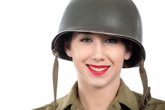 Una bella giovane donna vestita in uniforme militare wwii con casco Foto Premium