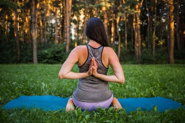 Una bella ragazza atleta si siede indietro ed esegue esercizi di yoga in natura Foto Premium