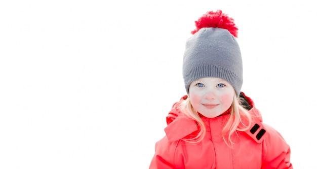 Una bella ragazza bianca con un cappello invernale e una tuta rosa, sorridendo e ridendo nella neve Foto Premium
