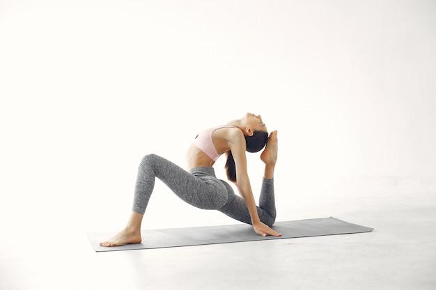 Una bella ragazza è impegnata in uno studio di yoga Foto Gratuite