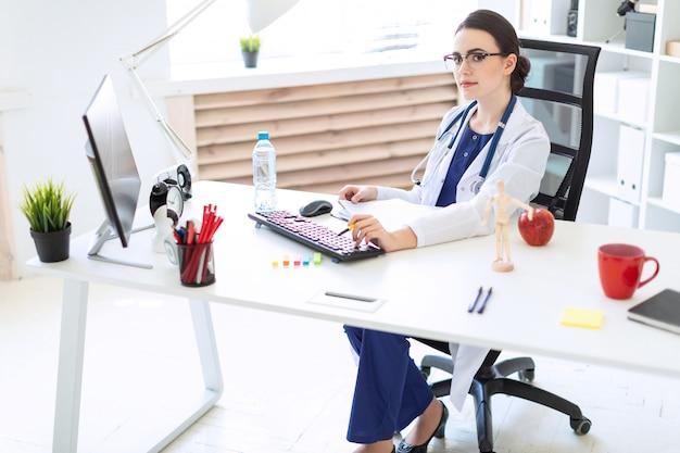 Una bella ragazza in abito bianco è seduta alla scrivania di un computer con documenti e una penna tra le mani. Foto Premium