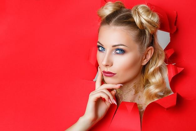 Una bella ragazza in salita da un buco in carta rossa Foto Premium