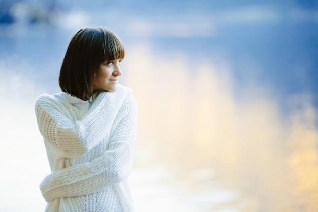 Una bella ragazza in un maglione bianco sorride Foto Gratuite