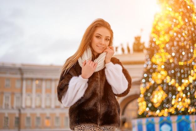 Una bella ragazza si erge sullo sfondo dell'albero di natale della città Foto Premium