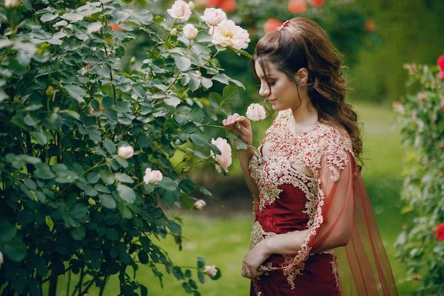 Una bella ragazza turca in un lungo abito rosso cammina nella città vecchia estate Foto Gratuite