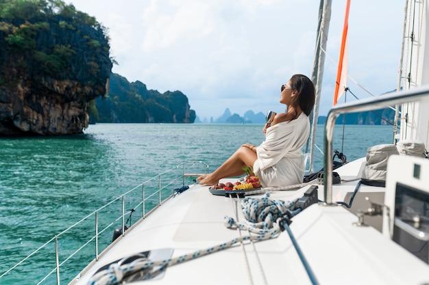 Una bella signora asiatica in una camicia bianca su uno yacht beve champagne e mangia frutta Foto Premium