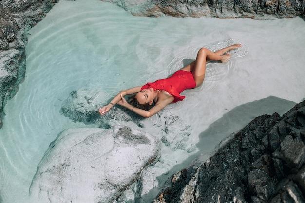 Una bellissima bionda snella in un costume da bagno rosso alla moda si trova nel mare, vicino alle rocce. moda tropicale. Foto Premium