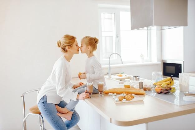 Una bellissima giovane madre con i capelli chiari in pizzo bianco e pantaloni blu jeans seduto a casa Foto Gratuite
