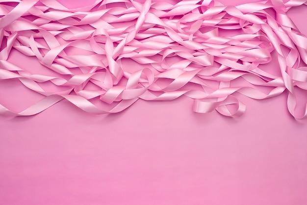 Una bobina di nastri decorativi di raso di colore rosa. Foto Premium
