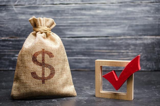 Una borsa con soldi e un segno di spunta rosso Foto Premium