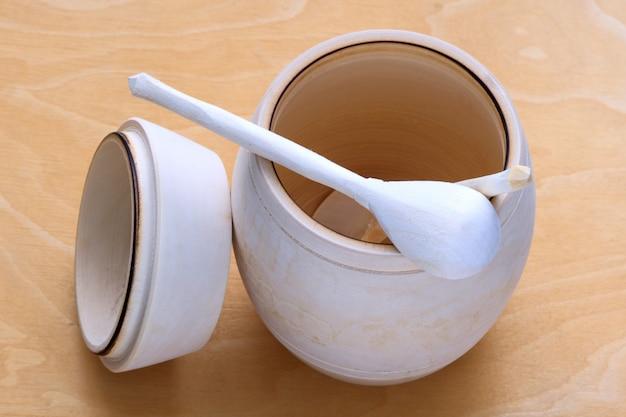 Una botte di miele con un cucchiaio Foto Premium