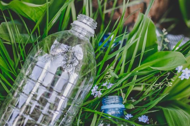 Una bottiglia di plastica giace sull'erba a terra, inquinamento ambientale, immondizia, rifiuti Foto Premium