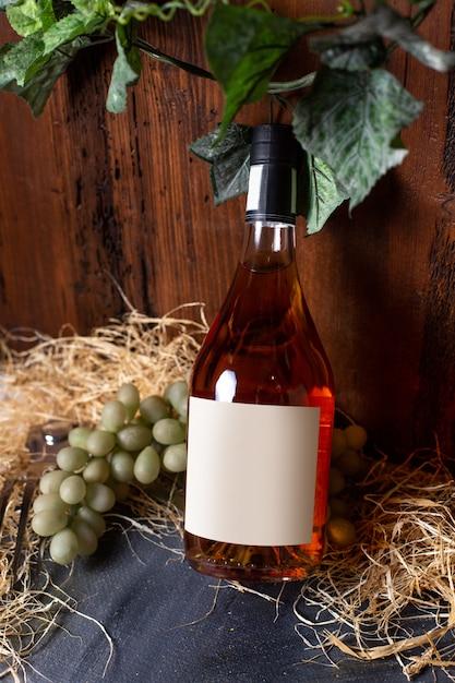 Una bottiglia di whisky vista frontale insieme con uva verde e foglie verdi isolatedo n sullo sfondo marrone bere alcolici in cantina Foto Gratuite