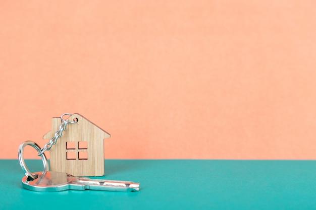 Una chiave su un portachiavi in legno a forma di casa Foto Premium